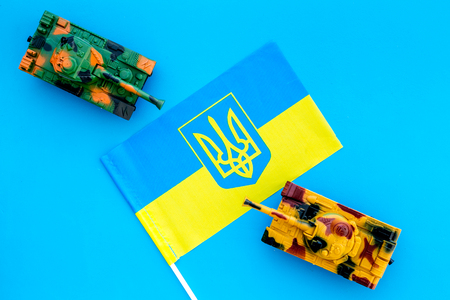 War, military threat, military power concept. Ukraine. Tanks toy near Ukrainian flag on blue background top view.