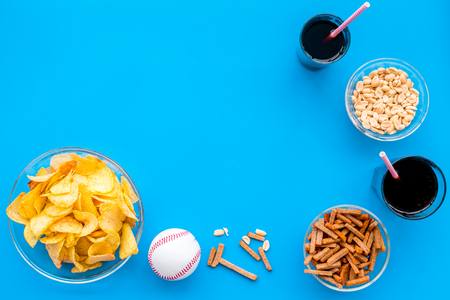 Snacks for TV watching. Chips, nuts, soda, rusks on blue background top view.