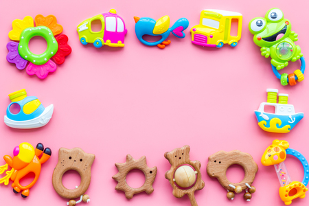 Handmade toys for newborn babies, plastic and wooden rattle on pink background top view. Stockfoto
