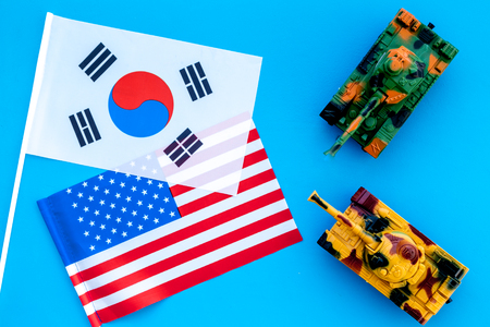 War, confrontation concept. Korea, USA. Tanks toy near Korean and american flag on blue background top view.