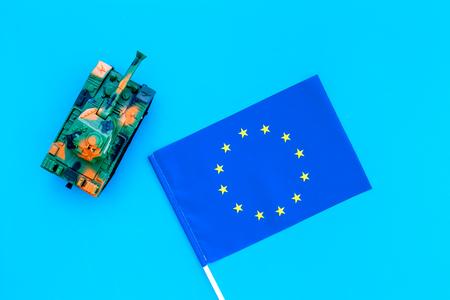 War, military threat, military power concept. European Union. Tanks toy near European flag on blue background top view.
