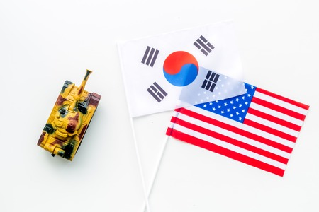 War, confrontation concept. Korea, USA. Tanks toy near Korean and American flag on white background top view