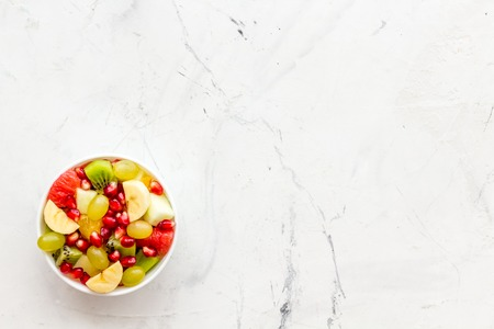 Fruit diet concept. Fruit salad with apple, kiwi and pomegranate in bowl on white stone background top view copy space