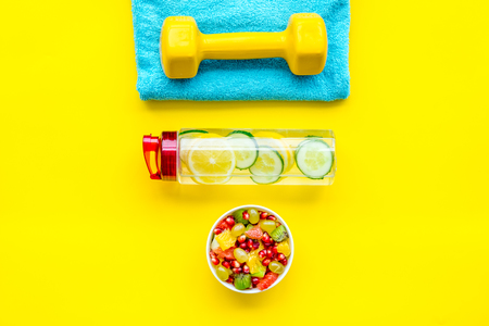 Healthy lifestyle, healthy habits. Detox water, fruit salad, sport equipment dumbbells on yellow background top view.