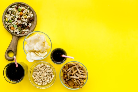 Snacks for TV watching. Chips, nuts, soda, rusks, dried fruits on yellow background top view copy space Stock Photo