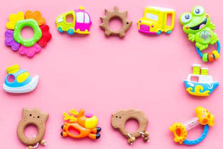 Jouets faits à la main pour les nouveau-nés filles, hochet en plastique et en bois sur fond rose vue de dessus espace pour cadre de texte