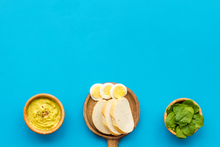 Healthy breakfast. Toasts with vegetables and guacamole on blue background top view space for text