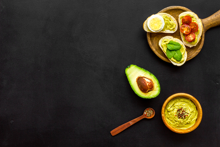 Make avocado bruschettas. Toasts with vegetables and guacamole on black background top view space for text Foto de archivo - 115957788