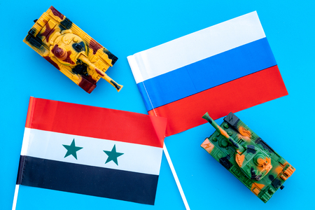 War, confrontation concept. Russia, Syria. Tanks toy near Russian and Syrian flag on blue background top view
