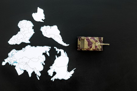 Military action, military threat concept. Tanks toy on world map on black background top view space for text Stock Photo