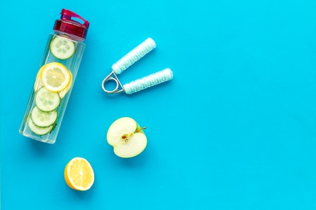 Healthy fruit water for sport, fitness. Bottle of water with lemon and cucumber near sport equipment on blue background top view copy space