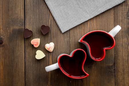 Valentines day concept. Heart-shaped mugs and sweets on dark wooden background top view copy space