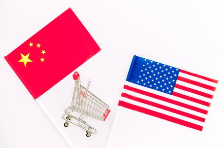 Handelskrieg zwischen den USA und China. Amerikanische und chinesische Flaggen in der Nähe von Einkaufsdiagrammen auf weißem Hintergrund, Draufsichtplatz für Text