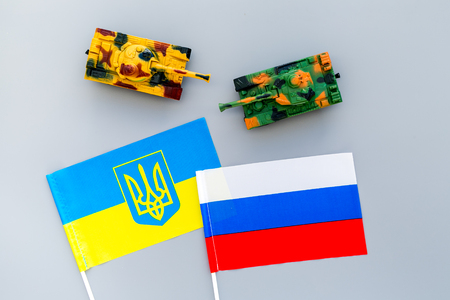 War, confrontation concept. Russia, Ukraine. Tanks toy near Russian and Ukrainian flag on grey background top view.