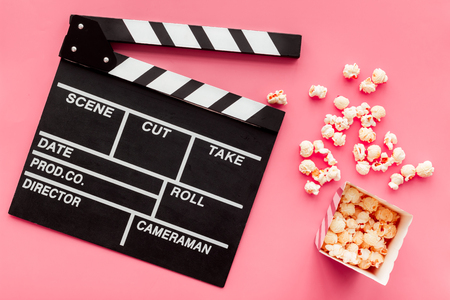 Film watching concept. Clapperboard and popcorn on pink background top view Banque d'images - 115957967