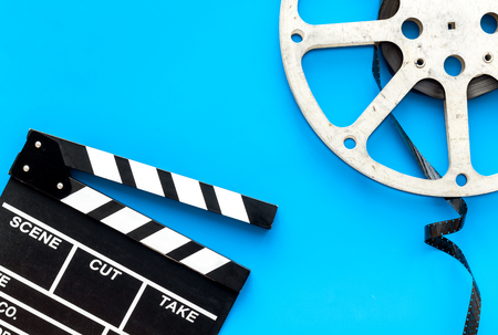 Filming concept. Clapperboard and film stock on blue background top view copy space Banque d'images - 115957941