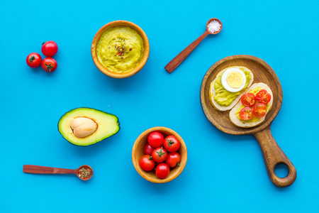 Make avocado bruschettas. Toasts with vegetables and guacamole on blue background top view Banque d'images - 116033044