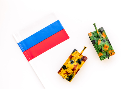 War, military threat, military power concept. Russia. Tanks toy near russian flag on white background top view