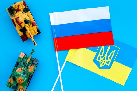 War, confrontation concept. Russia, Ukraine. Tanks toy near russian and Ukrainianflag on blue background top view Stock Photo