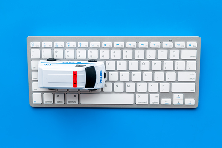 Call police online concept. Police car toy and computer keyboard on blue background top view