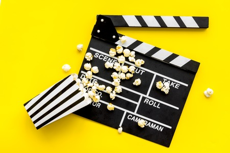 Movie premiere concept. Clapperboard and popcorn on yellow background top view