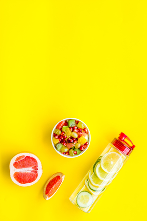 Diet rich in fruits. Slimming diet. Fruit salad near fruit lemon and cucumber water on yellow background top view copy space