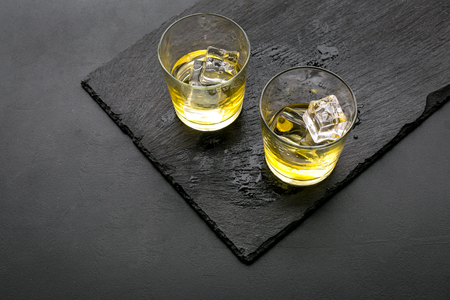 In the bar. Whiskey with ice on black desk on black background top view copy space