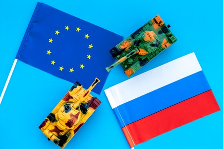 War, confrontation concept. European Union, Russia. Tanks toy near european and russian flag on blue background top view. Stock Photo - 116033191