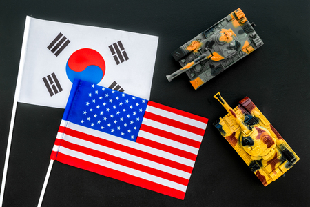 War, confrontation concept. Korea, USA. Tanks toy near korean and american flag on black background top view. Stock Photo