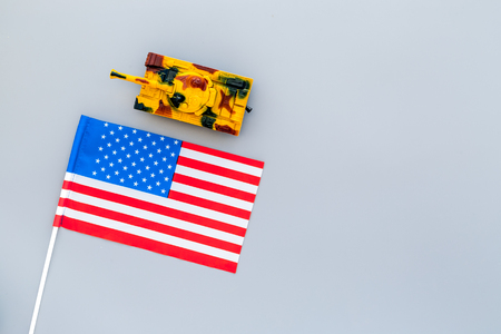 War, military threat, military power concept. USA. Tanks toy near american flag on grey background top view.