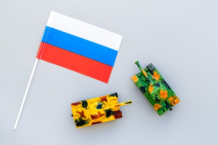 War, military threat, military power concept. Russia. Tanks toy near russian flag on grey background top view.