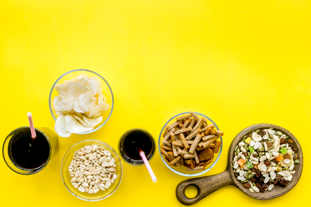 Snacks for TV watching. Chips, nuts, soda, rusks, dried fruits on yellow background top view.