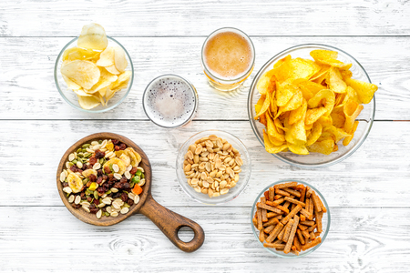Snacks and beer. Chips, nuts, rusks near beer on white wooden background top view.