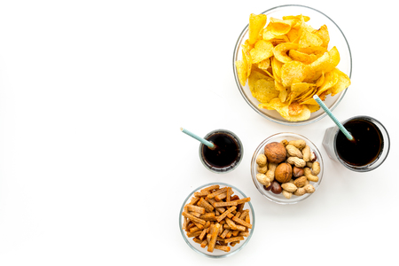 Snacks for TV watching. Chips, nuts, soda, rusks on white background top view.