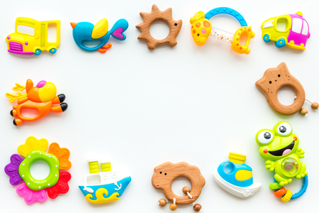 Handmade toys for newborn babies, plastic and wooden rattle on white background top view.