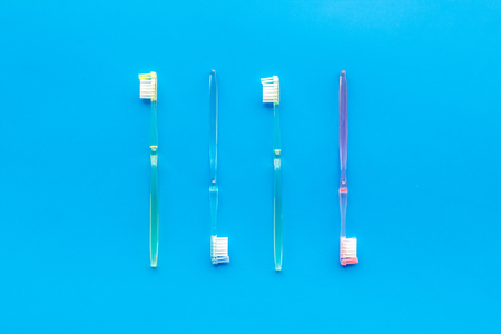Oral hygiene. Plastic toothbrushes on blue background top view.