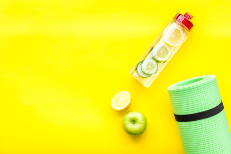 Healthy fruit water for sport, fitness. Bottle of water with lemon and cucumber near sport equipment on yellow background top view.