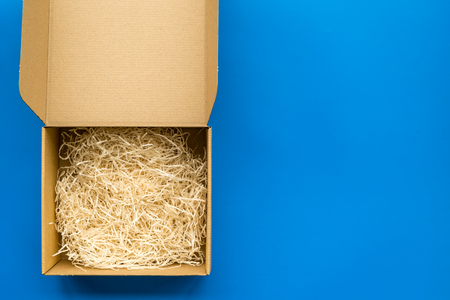 E-commerce. Delivery of goods that was purchased online. Empty cardboard box with cut paper on blue background top view.