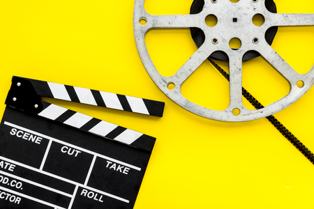 Filming concept. Clapperboard and film stock on yellow background top view space for text Banque d'images - 116083096