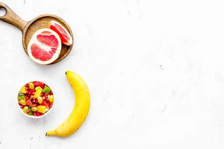 Healthy diet concept. Fruit salad near fresh fruits on white background top view copy space