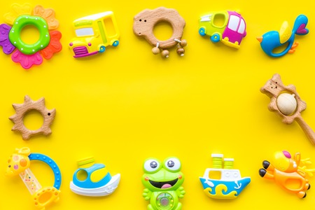 Handmade toys for newborn babies, plastic and wooden rattle on yellow background top view.