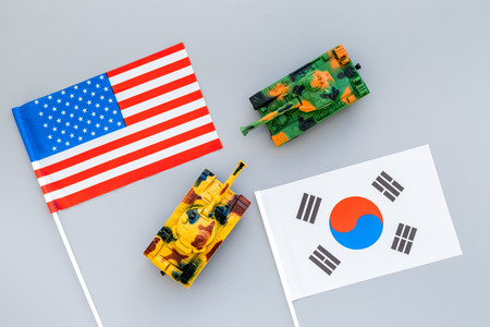 War, confrontation concept. Korea, USA. Tanks toy near Korean and american flag on grey background top view.