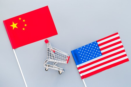 USA and China trade war. American and Chinese flags near shopping chart on grey background top view.
