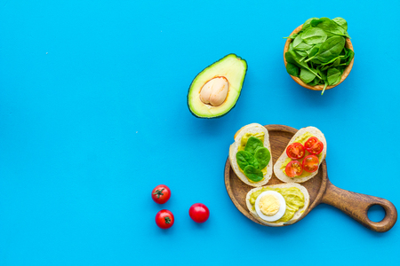 Make avocado bruschettas. Toasts with vegetables and guacamole on blue background top view. Stockfoto - 116150952