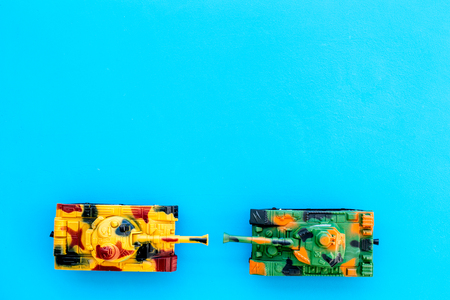 War concept. Tanks toy on blue background top view.