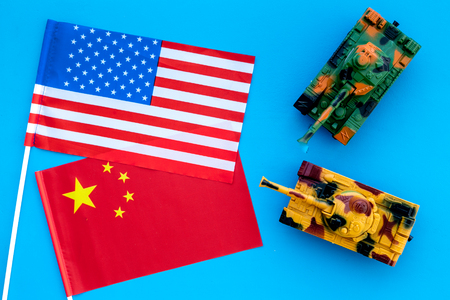 War, confrontation concept. China, USA. Tanks toy near Chinese and American flag on blue background top view.