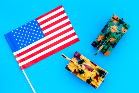 War, military threat, military power concept. USA. Tanks toy near American flag on blue background top view.