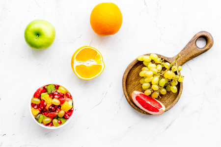 Healthy diet concept. Fruit salad near fresh fruits on white background top view. Stock Photo
