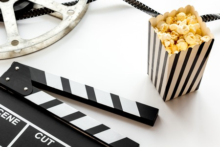 Cinema concept. Clapperboard, film stock and popcorn on white background. Banque d'images - 116152915