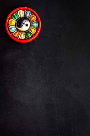 Buddhist symbol. Yin Yang symbol on black background top view copy space